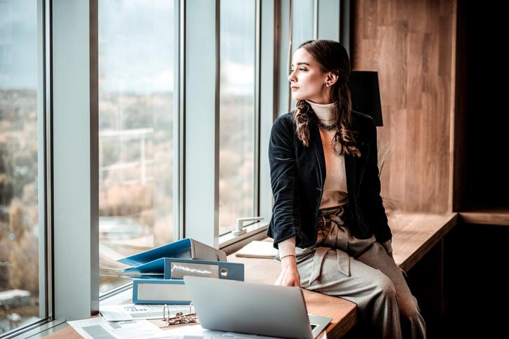 Mulher pensando em como administrar sua vida pessoal e profissional